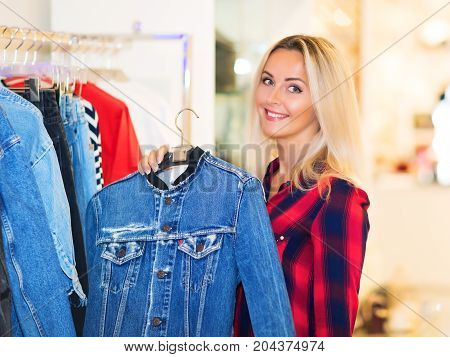 Young blonde smiling attractive woman with long hair shopping in the fashion wear garments apparel store and choosing a jeans jacket