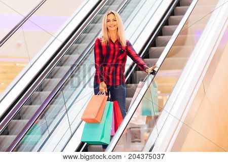 Young blonde smiling attractive woman with long hair with a lot of color shopping bags on escalator in the fashion store