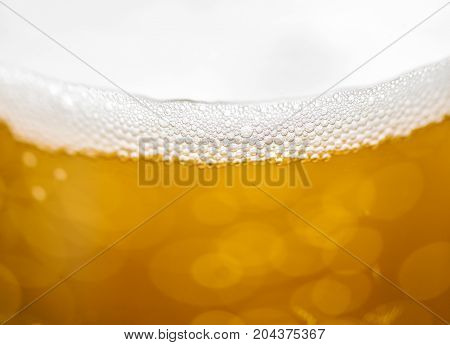 Blured beer background with some floating bubbles.