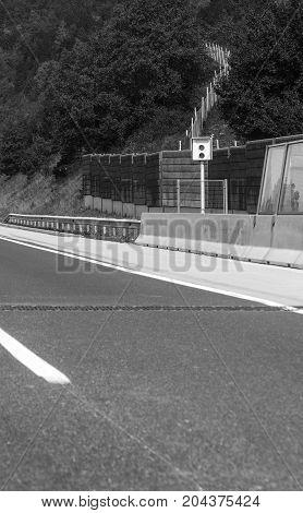 Stationary car speed radar near a highway road.
