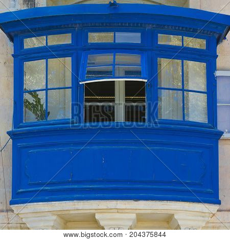 Building with traditional colorful maltese balcony in historical part of Valletta.