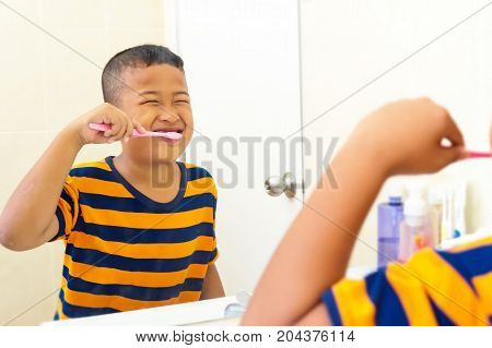 Asian boy brushing teeth in bathroom with tooth brush healthy lifestylechild dental care oral hygiene concept.