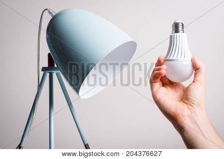 Changing the bulb for led bulb in table lamp in turquoise colours.