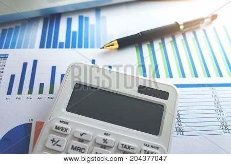 Close up of business pen and white calculator on financial graph data with laptop. finance saving investment business and banking concept.