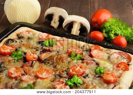 Homemade pizza with tomatoes mushrooms sausage and cheese over wooden background selective focus