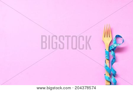 Blue Measuring tape wrapped around wood fork lying on colorful pink background. Diet and Healthy Concept.