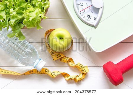 Green apple and Weight scalemeasure tap with fresh vegetable clean water and sport equipment for women diet slimming. Diet and Healthy Concept