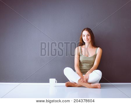 Portrait of a happy woman sitting on the floor on gray background.