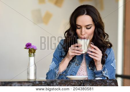 Woman Sitting Indoor In Urban Cafe Wearing Casual Clothes