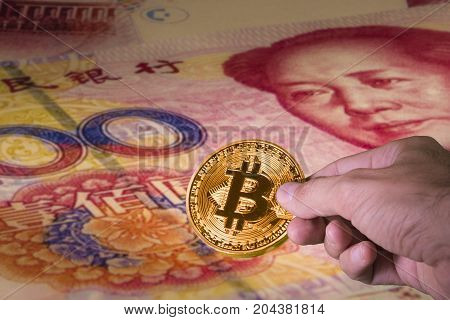 Financial concept with golden Bitcoin on 100 yuan or renminbi banknote, Chinese Currencies