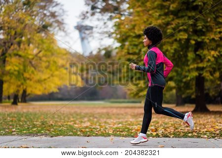 Athletic female jogger running along the pathway