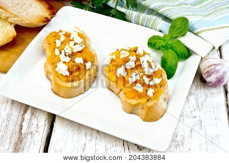 Bruschetta with pumpkin, salted feta cheese in a plate, garlic, basil and parsley, napkin and orange vegetable on a wooden board background