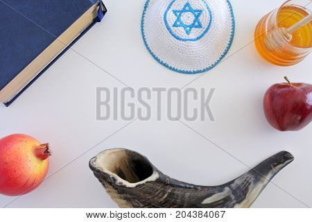 Flat Lay View Of Shofar, Torah Book, Kippa, Apple, Honey And Pomegranate Background