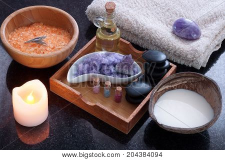 A coconut shell with milk alongside a spa treatment set with orange bath salt, purple massage salt, hot stones, aromatic oil and soft towels