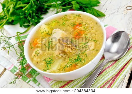 Soup fish kulesh with millet, potatoes and carrots in a white bowl on a napkin, parsley, dill on a wooden board background
