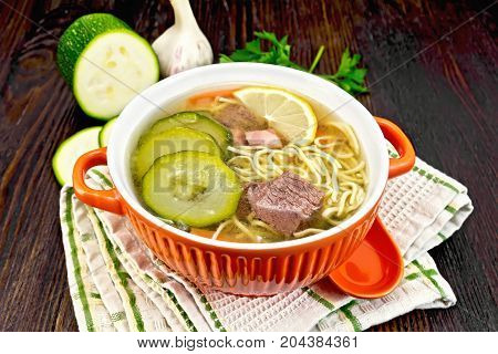 Soup with zucchini, beef, ham, lemon and noodles in a bowl, parsley and dill on a towel on a wooden board background