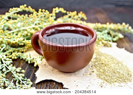 Herbal tea in a clay cup, twigs gray sagebrush, wormwood dried on rough paper on the background of wooden boards