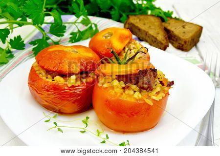 Tomatoes stuffed with meat and steamed wheat bulgur, a sprig of thyme in a plate, napkin, fork, bread and parsley on the background light wooden boards
