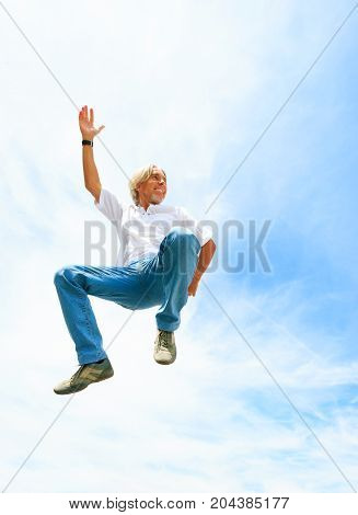 man in his 50s jumping high into the sky