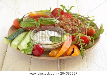 Plate with three healthy different dips and vegetables