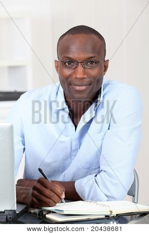 Office worker writing on agenda