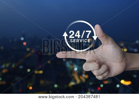 24 hours service icon on finger over blur colorful night light city tower Full time service concept