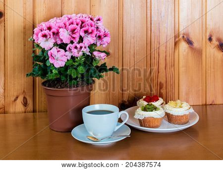 Cup of coffee sweet cakes with fruits and pelargonia flower on wooden table