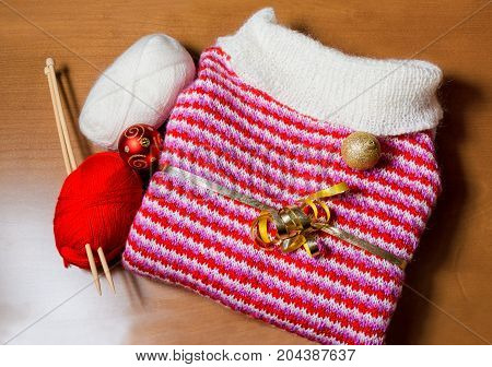 Christmas and winter time decoration and gift. Warm red and white knitted sweater and christmas ball on wooden background.