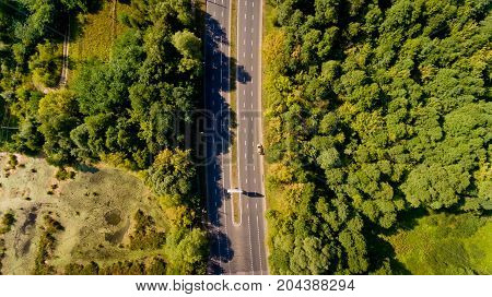Top view of asphalt road passes through the field and forest.