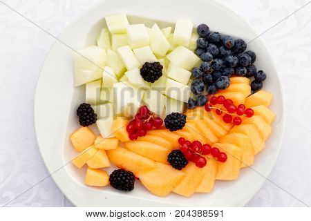 Selection Of Cut Up Fruit And Berries On A White Ceramic Plate From Above.