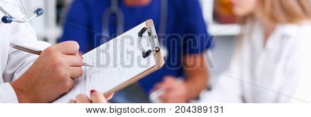 Female Doctor Hold Clipboard Pad And Fill Medical History