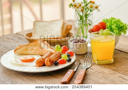 Homemade breakfast with sunny side up fried egg toast sausage fruits vegetable strawberry jam and orange juice in side view with copy space. Delicious homemade american breakfast concept for background. American breakfast on breakfast table.