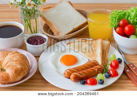 Homemade breakfast with sunny side up fried egg toast sausage fruits vegetable strawberry jam and orange juice in top view with copy space. Delicious homemade american breakfast concept for background. American breakfast on breakfast table.