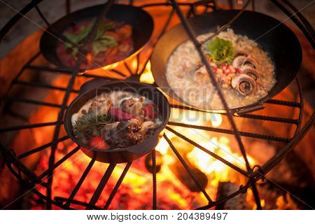 cooking a meat dish and a soup on the fire