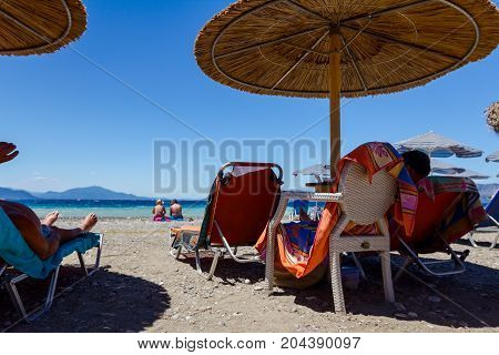 People tourists are on public beach with thatched umbrellas and loungers next to the coastline.
