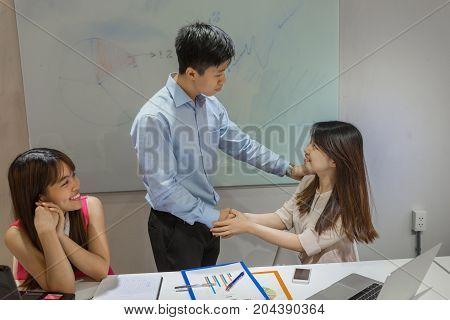 Supervisor congratulate his junior colleague on her promotion