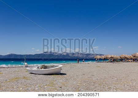 Small boat is dry docked withdrawn at the beach coastline.