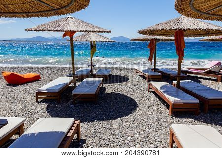 Luxury and comfortable mattress sunbed under sunshades is placed on the sunny beach.