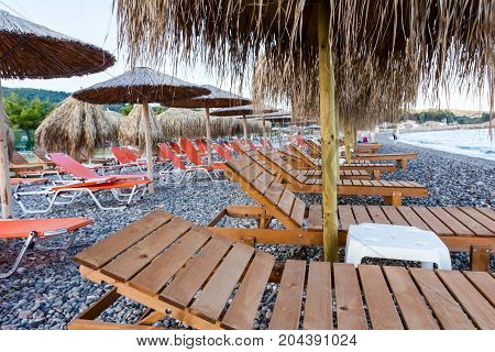Wooden sunbed under thatched sunshades is placed on the morning beach.