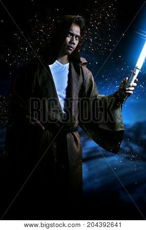 young warrior with brown hooded cape holding a light saber