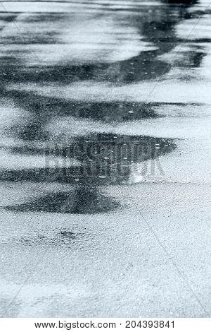 Rain Falling On Asphalt Road Creating Water Puddles