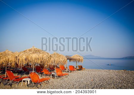 Sunshades made of straw umbrellas and plastic deckchairs for a perfect holiday.