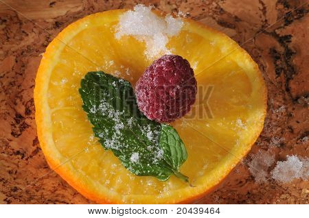 Raspberry And Mint Leaf On A Frozen Slice Of Orange