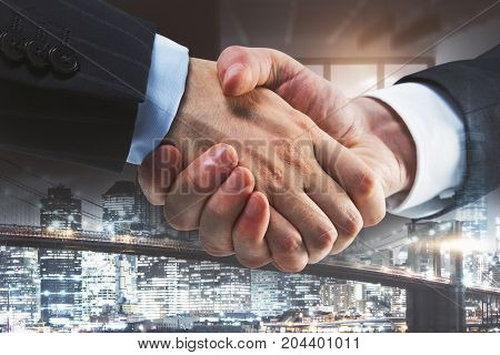 Side view of creative handshake on night city background. Teamwork concept. Double exposure