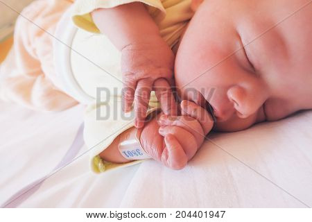 Newborn baby first days of life in delivery room. Infant asleep in hospital after childbirth. New born close-up with name tag bracelet. poster