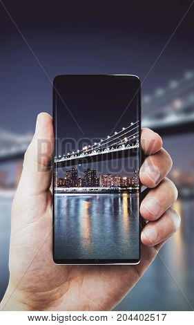 Man taking night city photograph with smartphone. Contemporary concept