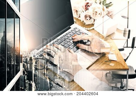 Side view of female hands using laptop with empty screen placed on wooden girly desktop. City background. Mock up Double exposure