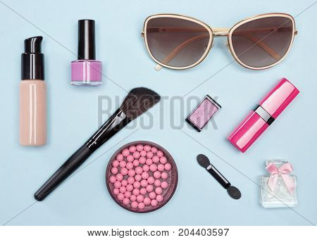 Set of cosmetic bag essentials for urban life: foundation, blush, lipstick, eyeshadow, makeup brushes, perfume, nail polish, sunglasses