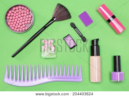 Set of cosmetic bag essentials: foundation, blush, lipstick, eyeshadow, makeup brushes, perfume, nail polish, comb