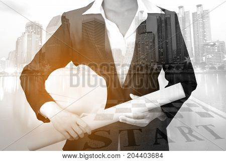 Double exposure of architecture in a suit with safety helmet and engineering drawing on city background industrial concept.